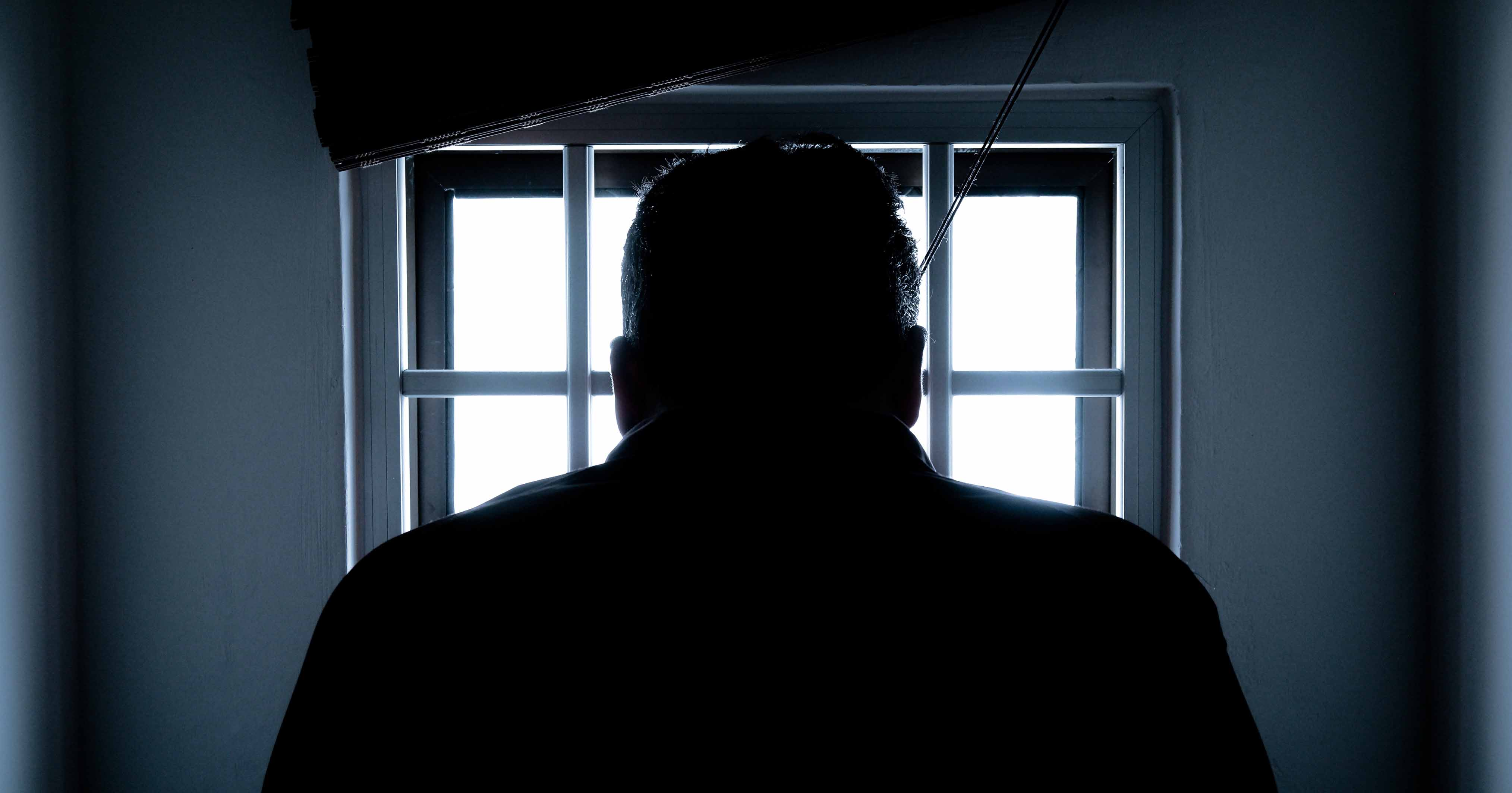 Man silhouetted against a window.