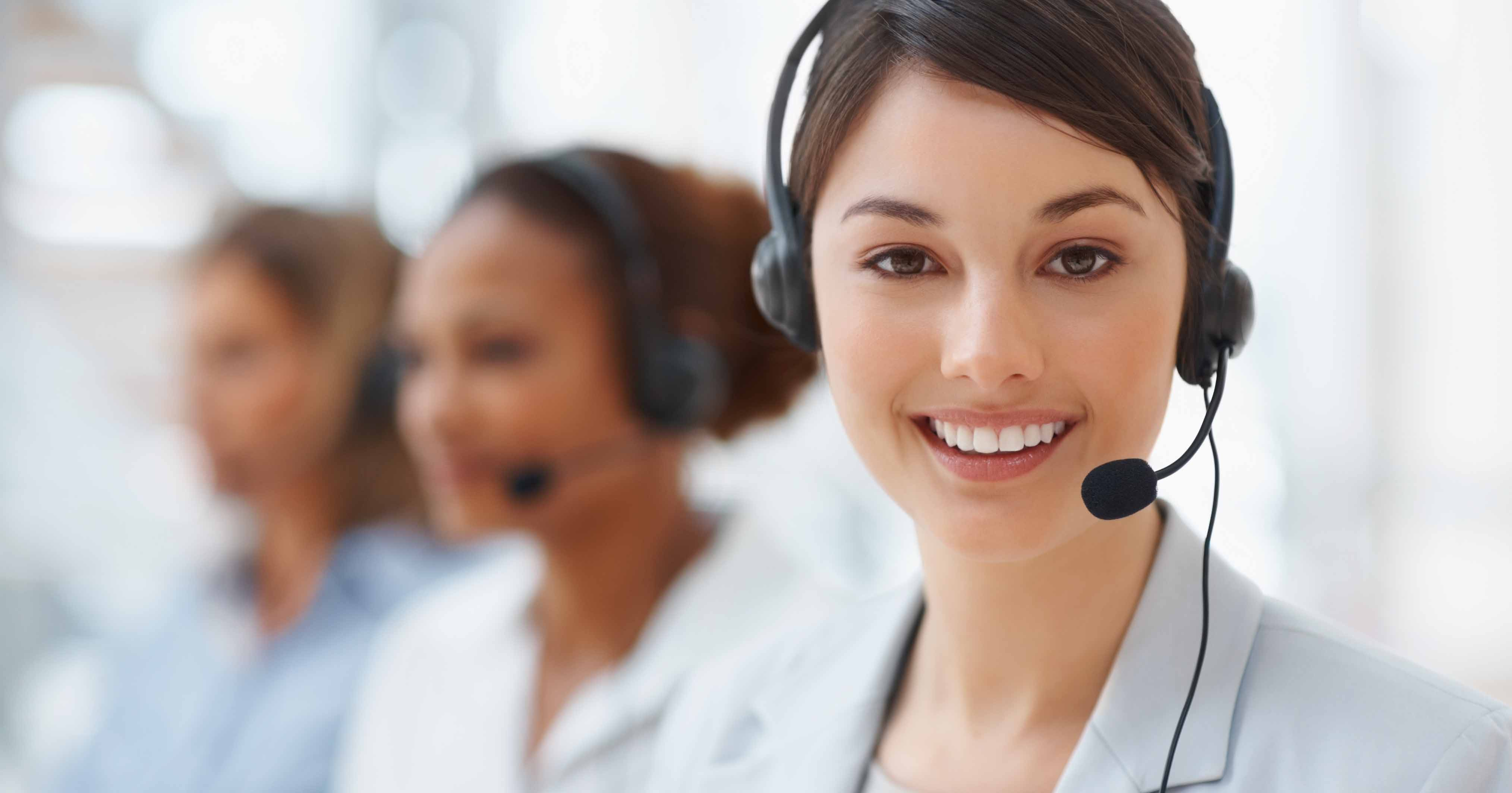 Image of a woman working in a call centre, smiling.